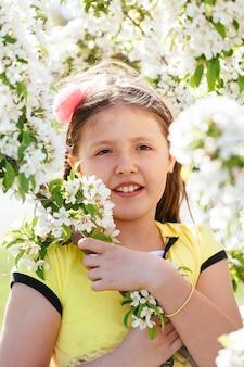 Bella ragazza, cammina con un bouquet in un bellissimo vestito nel parco, bella luce serale sullo sfondo