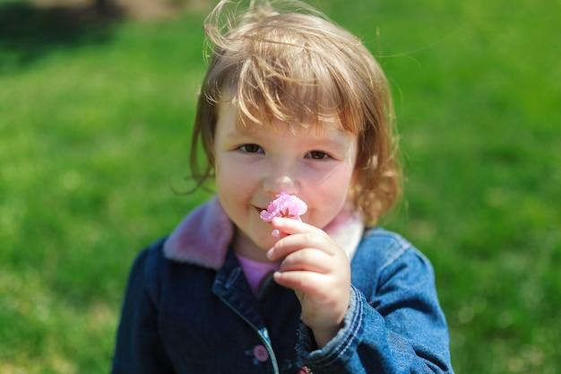 Bella ragazza, cammina con un bouquet in abito nel parco, luce della sera sullo sfondo