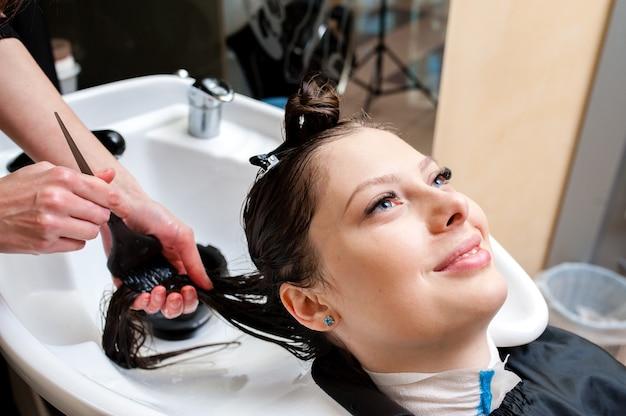 Bella ragazza che si lava i capelli.