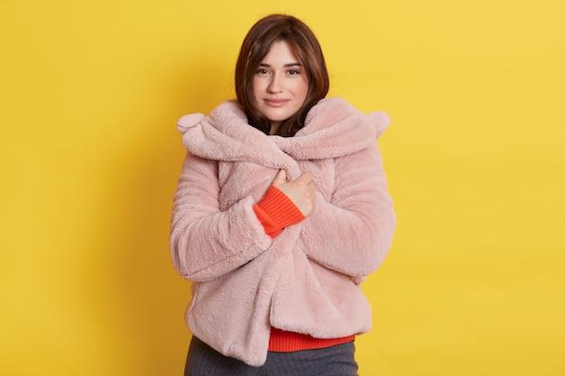 Bella ragazza che indossa un cappotto di pelliccia rosa pallido, si sente accogliente e calda, adorabile donna con un'espressione facciale sognante, in posa isolata sopra il muro giallo.