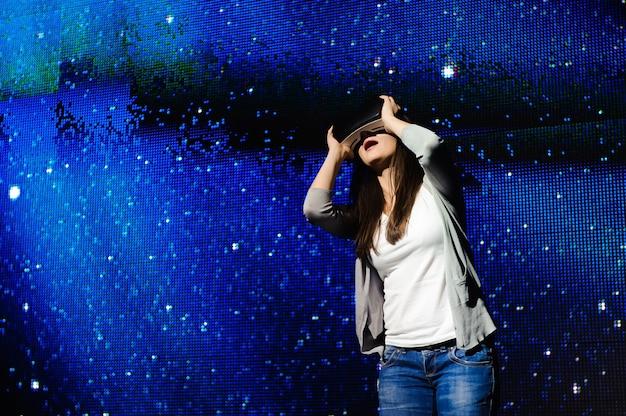 Una bella ragazza che indossa un dispositivo di realtà virtuale, in piedi sullo sfondo del cielo.