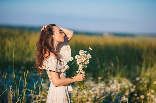 Bella ragazza nel campo di grano con grano maturo nelle mani