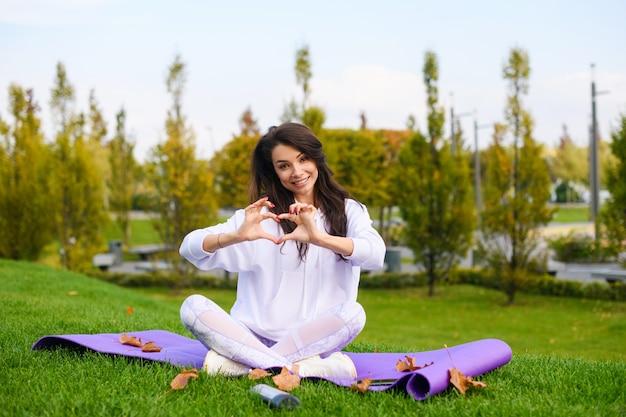 La bella ragazza in vestiti bianchi si siede alla stuoia di sport nella posa del loto e mette le dita nella forma del cuore, forma fisica di amore, yoga, concetto di allenamento all'aperto