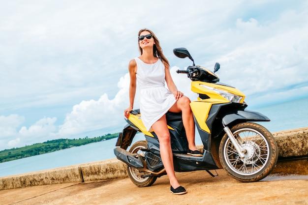 La bella ragazza in un vestito bianco si siede su uno scooter sul fondo blu del mare