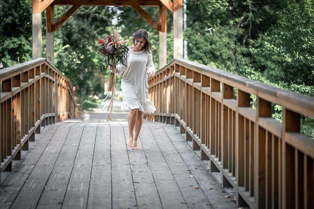 Bella ragazza in abito bianco con un mazzo di fiori esotici su un ponte di legno.