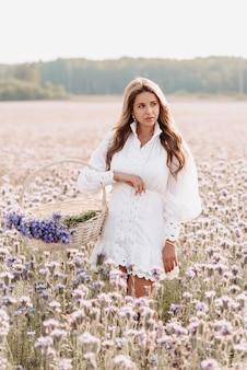 Bella ragazza in un abito bianco con un mazzo di fiori in un cesto in un campo in estate