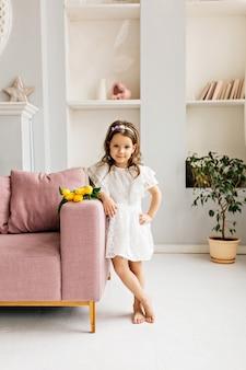 Una bella ragazza in abito bianco con un mazzo di tulipani è in piedi accanto a lei sul divano della stanza.
