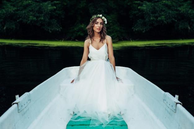 Una bella ragazza in un abito bianco e una corona di fiori si trova in una barca sul fiume