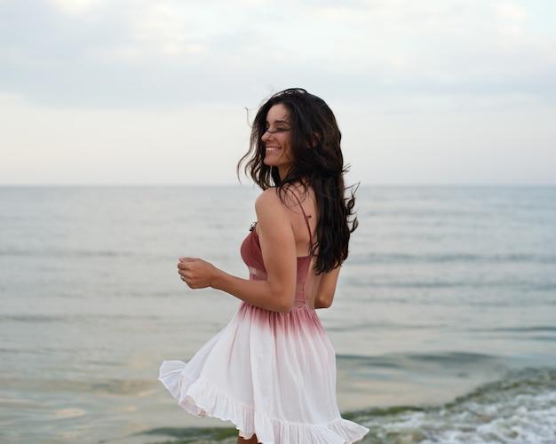 Una bella ragazza in un vestito bianco volante in riva al mare