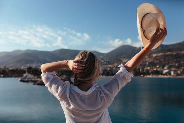 La bella ragazza in una camicia bianca che alza il suo cappello guarda il mare e le montagne