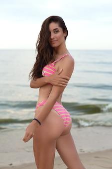 Bella ragazza in bianco in costume da bagno in riva al mare