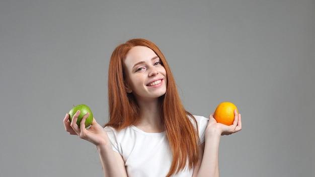 Bella ragazza in una maglietta bianca sorridente che tiene una mela in una mano e un pompelmo nell'altra, su uno sfondo grigio. cibo sano, frutti deliziosi