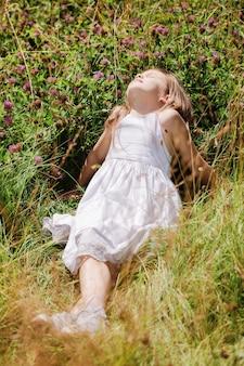 Bella ragazza in fiori di campo che riposa in una giornata di sole nel prato