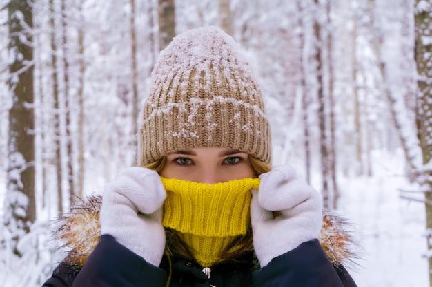 La bella ragazza nella foresta invernale nasconde il viso in un colletto di un maglione, riscaldata dal suo respiro