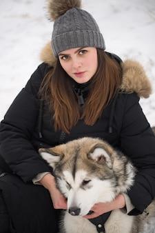 Bella ragazza nella foresta invernale con un cane