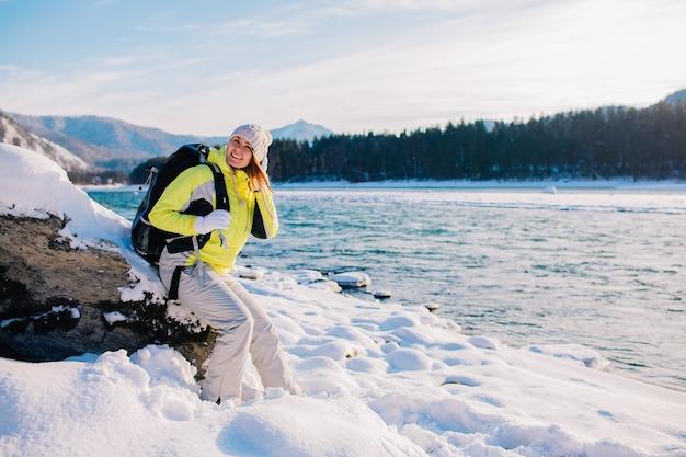 Bella ragazza con uno zaino che riposa su una roccia vicino a un fiume di montagna in una giornata invernale