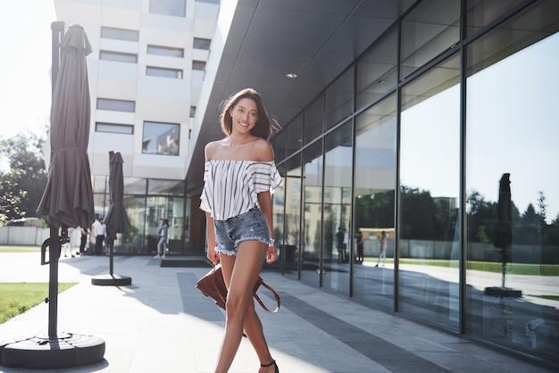 Bella ragazza con uno zaino, camminando lungo la strada della città in una mattina di sole.