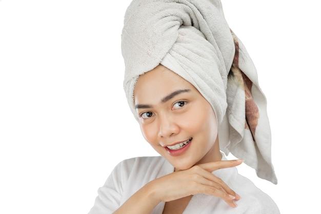 Bella ragazza con l'asciugamano sulla testa che sorride con le mani sotto il mento