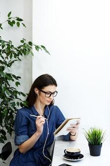 Bella ragazza con i capelli neri che indossa camicia blu spogliata e occhiali da vista seduto al bar con il telefono cellulare e la tazza di caffè, concetto di freelance, ritratto, ascolto di musica, scrittura in un blocco.
