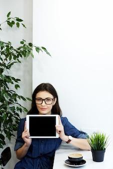 Bella ragazza con i capelli neri che indossa camicia blu spogliata e occhiali da vista seduti al caffè con tavoletta e tazza di caffè, concetto di freelance, mostrando un tablet, mock up.