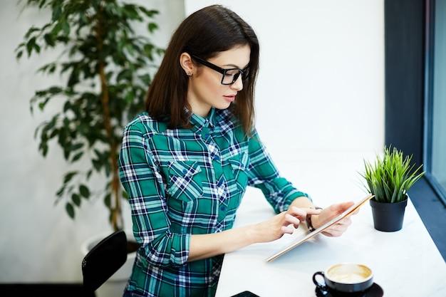 Bella ragazza con i capelli neri che indossa camicia e occhiali da vista seduti nella caffetteria con tavoletta e tazza di caffè, concetto di freelance, ritratto.