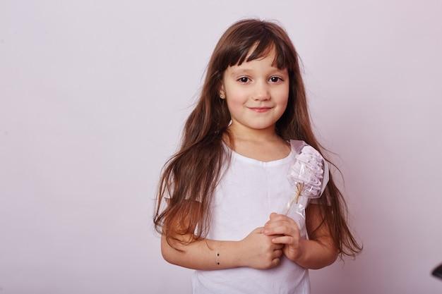 Bella ragazza con i capelli biondi mangia una lecca-lecca, caramello rotondo sul bastone nelle mani della ragazza sorridente allegra. la bambina con i capelli lunghi in maglietta bianca lecca la lecca-lecca. russia, sverdlovsk, 1 dicembre 2018