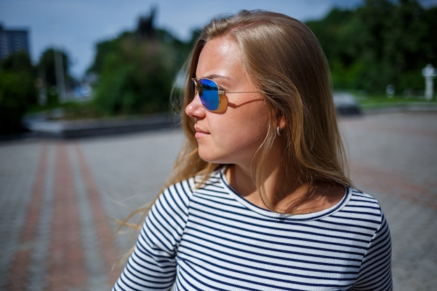 Una bella ragazza con i capelli lunghi biondi di aspetto europeo. vestito con jeans e maglietta. cammina in una giornata di sole