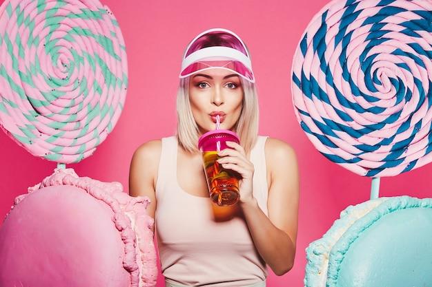 Bella ragazza con capelli biondi che indossa top e berretto rosa in piedi con enormi lecca-lecca dolci al rosa