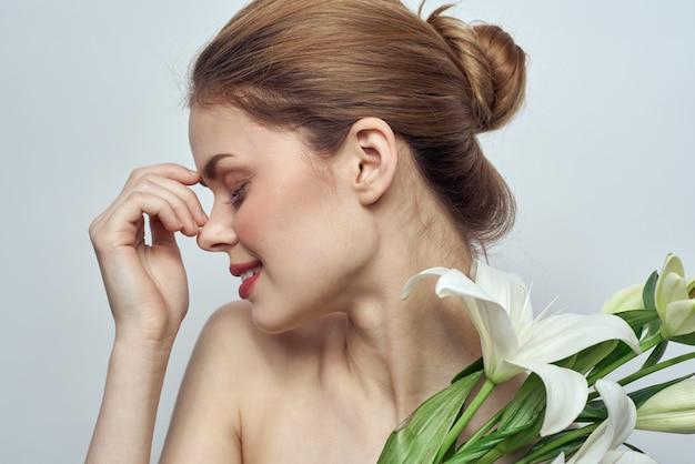 Bella ragazza con un mazzo di fiori bianchi su sfondo chiaro spalle nude pelle pulita primavera