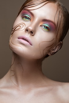 Bella ragazza con trucco dai colori vivaci e ciocche di capelli bagnati sul viso.