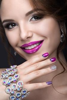 Bella ragazza con un trucco da sera luminoso e manicure viola con strass. design delle unghie. fronte di bellezza. foto scattata in studio su sfondo nero.