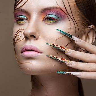 Bella ragazza con trucco luminoso alla moda, acconciatura creativa, unghie lunghe.