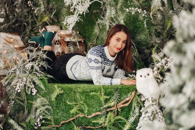 Bella ragazza con capelli castani in maglione blu e bianco con sorrisi di stampa natalizia