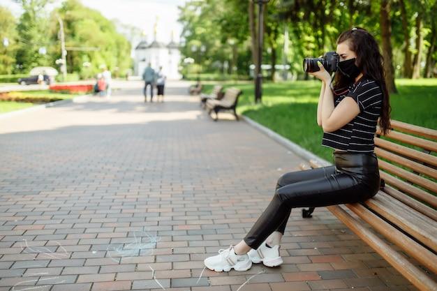 La bella ragazza con una macchina fotografica indossa una maschera medica e scatta foto nel parco. scoon polmonite ncov 2019 di coronavirus