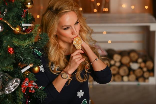 La bella ragazza con le mani dei biscotti si siede vicino ad un albero di natale