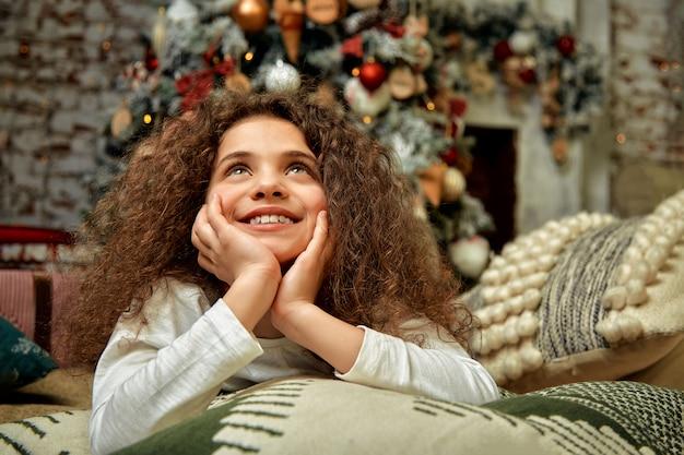 Bella ragazza con riccioli sullo sfondo di decorazioni natalizie, giace sul pavimento e sogni, in posa magnificamente verso la telecamera. aspettando un miracolo, fine natale e capodanno.