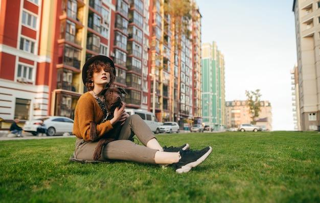 Bella ragazza con i capelli ricci e un cane in mano si siede in cortile