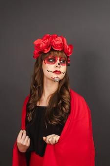 Bella ragazza con il trucco dia de los muertos ricoperta da un mantello rosso con sfondo grigio.