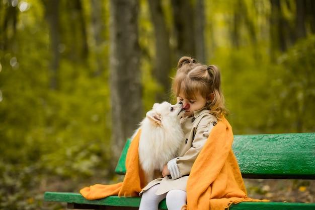 La bella ragazza con un cane è seduta su una panchina nel parco