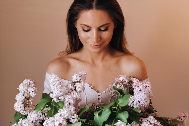 Bella ragazza con fiori lilla nelle sue mani. una ragazza con fiori lilla in primavera a casa. una ragazza con i capelli lunghi e il lilla tra le mani.