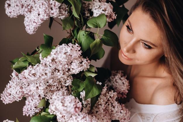 Bella ragazza con fiori lilla nelle sue mani