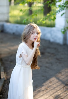 Una bella ragazza con lunghi capelli biondi di 8 anni si trova in un abito di seta bianca tiene misteriosamente un dito vicino alla bocca