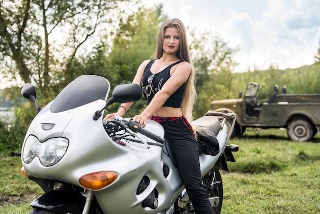 Bella ragazza con i capelli lunghi in posa in una moto
