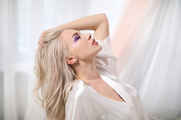 Bella ragazza con il trucco in abiti bianchi, ritratto di profilo.