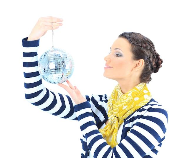 Bella ragazza con una sfera a specchio su uno sfondo bianco.