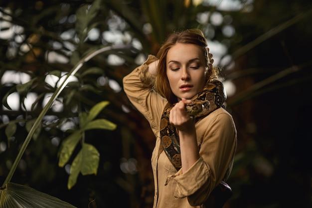 Una bella ragazza con trucco naturale e capelli rossi si trova nella giungla tra piante esotiche con serpente.