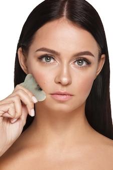 Bella ragazza con trucco naturale e pelle pulita tiene in mano uno scrubber viso giada per il dimagrimento delle rughe anti invecchiamento