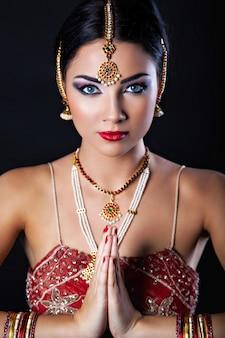 Bella ragazza con trucco orientale e gioielli indiani, look alla moda