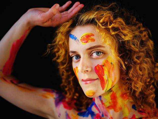 Bella ragazza con la vernice sul viso e sul corpo