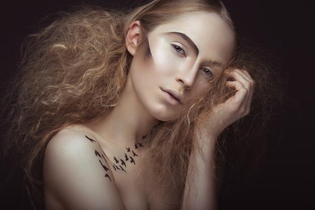 Bella ragazza con un motivo sul corpo a forma di uccelli, trucco creativo e acconciatura lussureggiante.